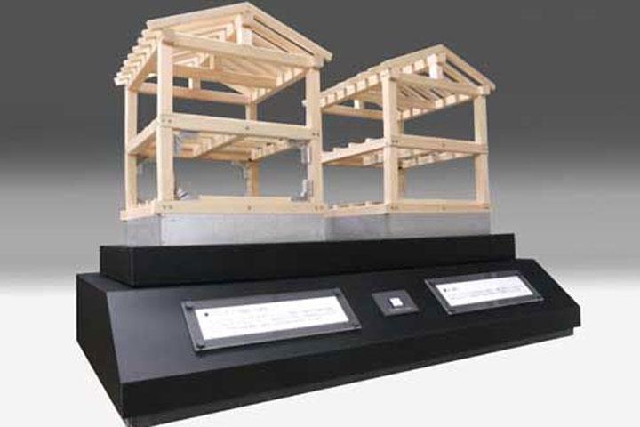 軸組みの住宅模型を電動で揺らし倒壊させる